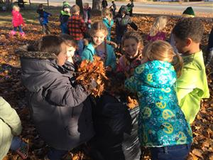 Using teamwork to fill garbage bags with leaves.